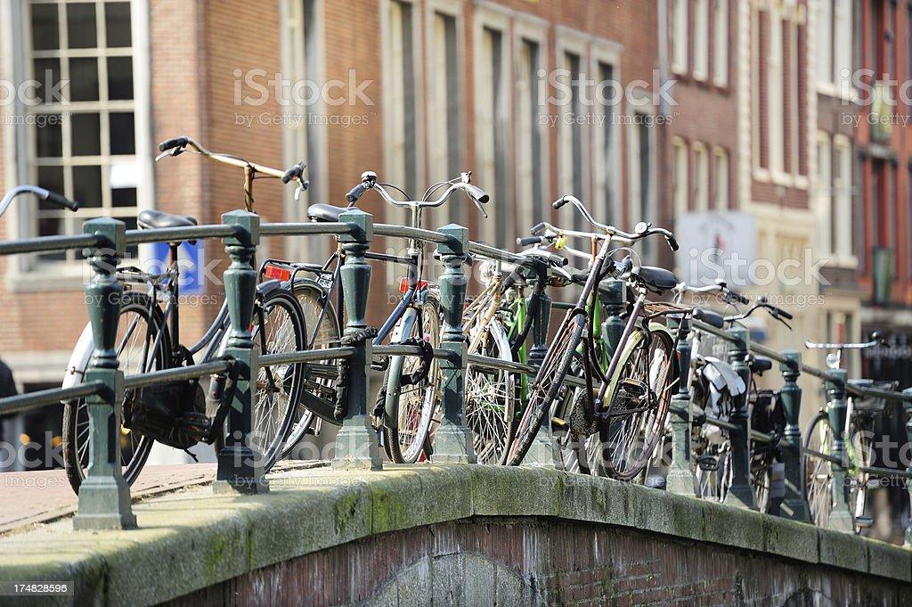 Bicycles parked on Amsterdam bridge, it's springtime royalty-free stock photo