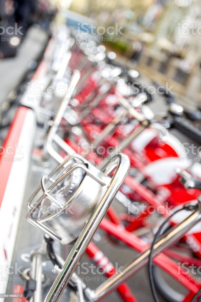 Bicycles stand in a row on a parking for rent. stock photo