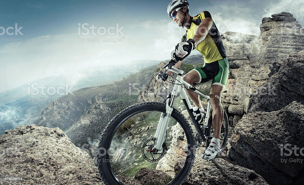 Bicyclist about to ride down a rugged extreme mountain stock photo