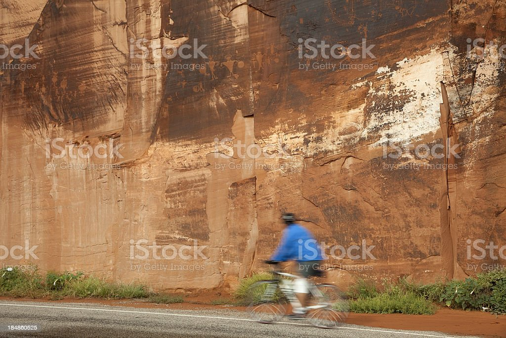 Bicyclist and sandstone cliff wall of Native American petroglyphs Utah royalty-free stock photo