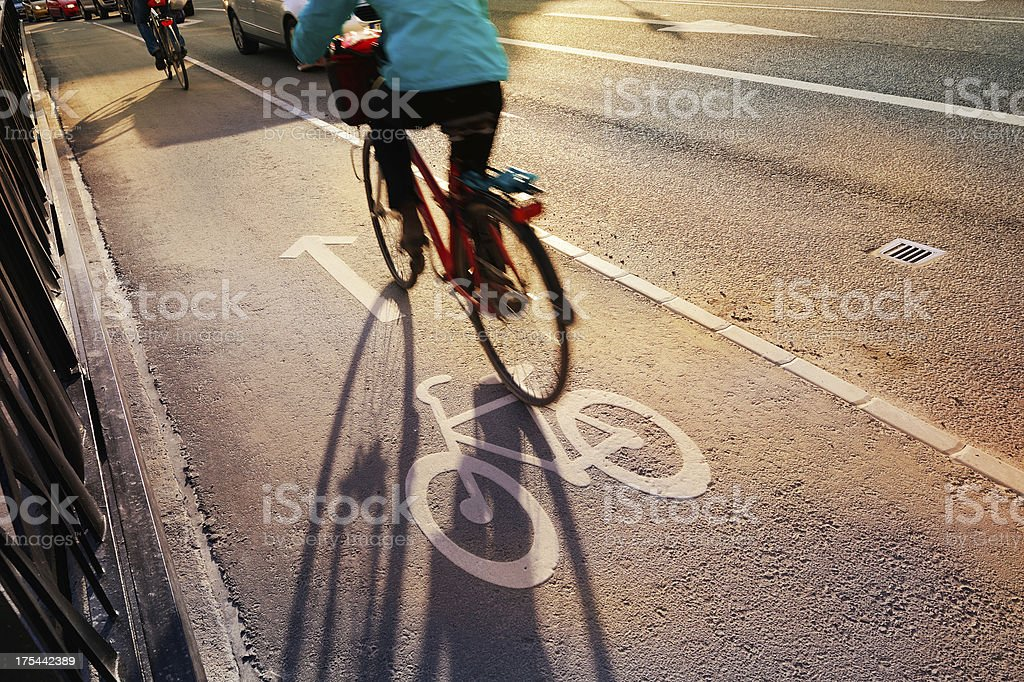 Bicyclist crossing bridge in bike lane stock photo
