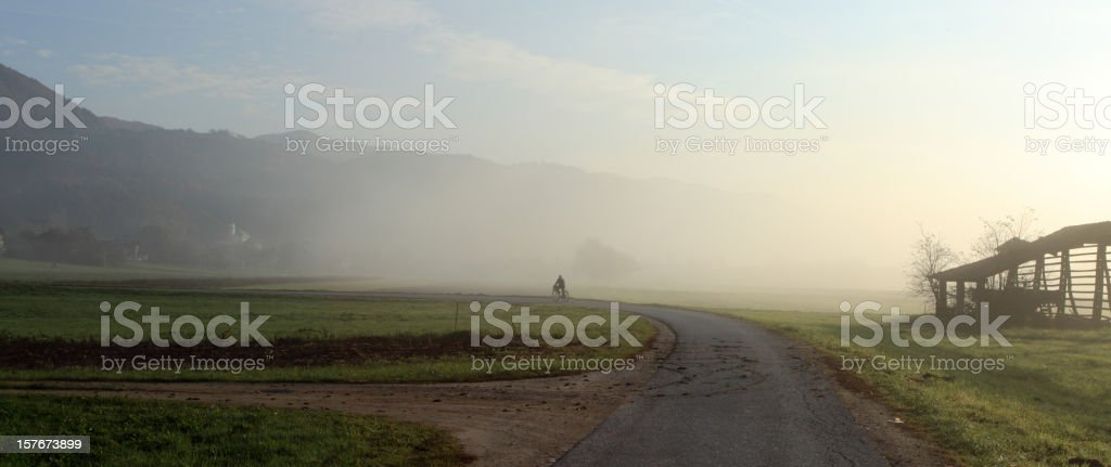 Bicyclist in the morning fog stock photo
