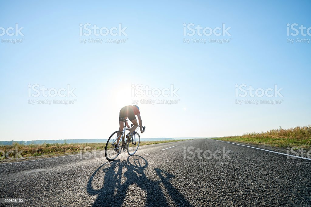 Bicyclist on open road stock photo