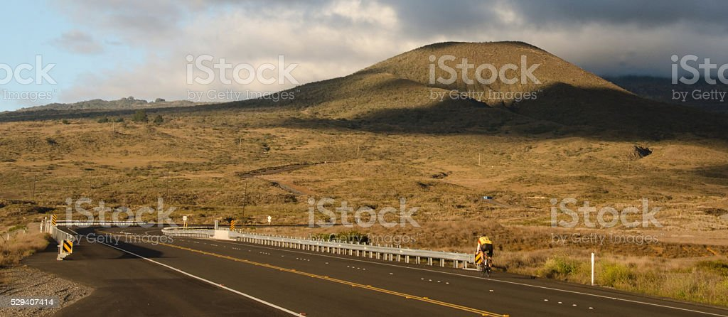 Bicyclist riding near sunset on route 200 stock photo