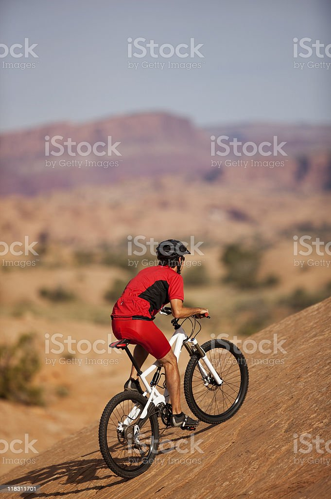 Bicyclist Riding Up Steep Hill On Slickrock Trail royalty-free stock photo