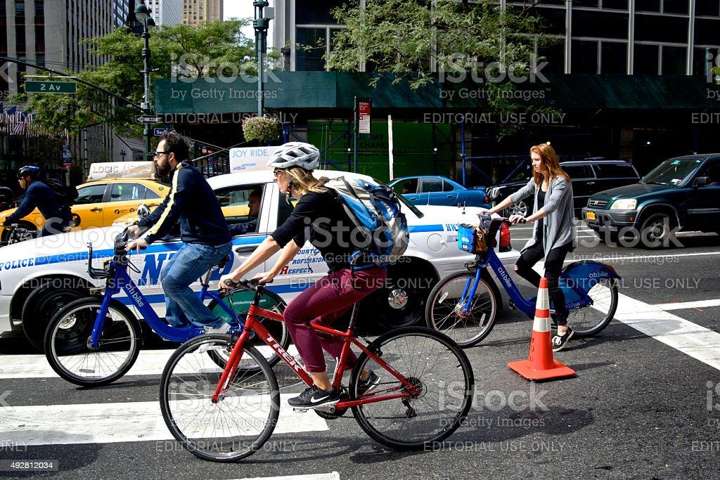 Bicyclists Passing NYPD Vehicle, Midtown Manhattan, New York City stock photo