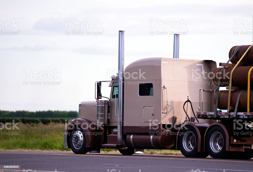 Big American classic rig semi truck transporting big pipes stock photo