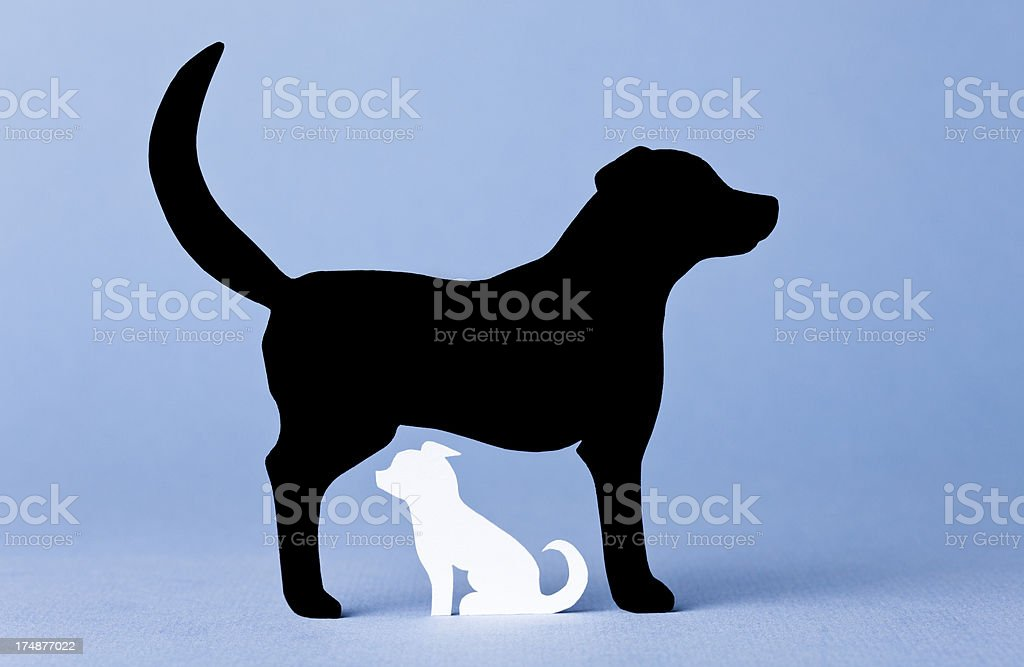 Big and small dog on blue background - paper concept royalty-free stock photo