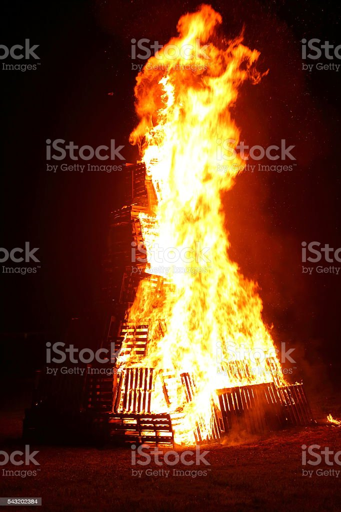 Big and tall wooden pallets bonfire in summer close-up stock photo