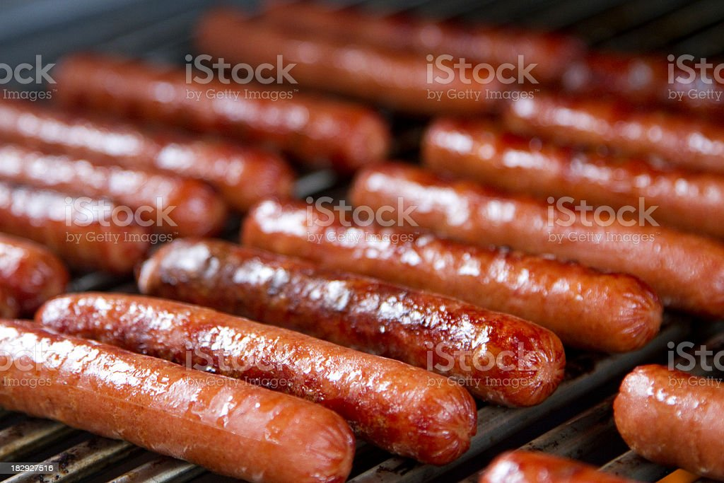 Big batch of hotdogs grilling on the grill stock photo