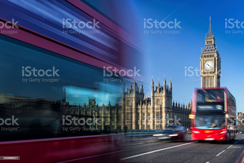 Big Ben and passing red buses, London, United Kingdom stock photo