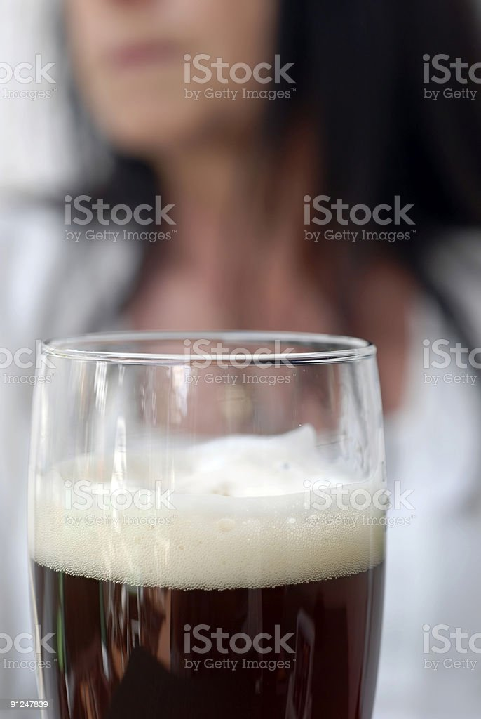 Big black beer and a woman close-up royalty-free stock photo