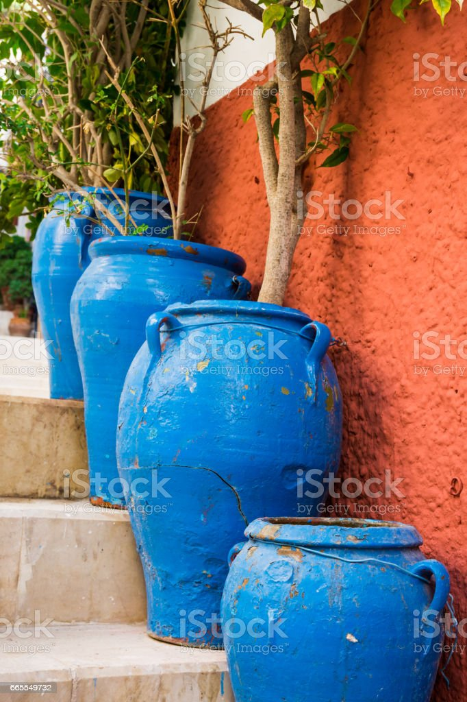 Big blue floor flowerpots with green plants in mediterranean style on staircase of an old town of European city, Spain, Costa Blanca stock photo