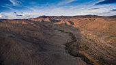 Big blue sky, desert mountains and a small stream.
