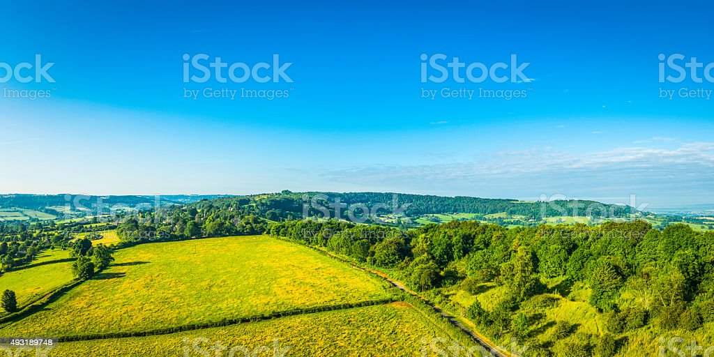 Big blue summer skies over green fields woods aerial panorama stock photo