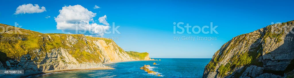 Big blue summer skies over ocean cove beach cliffs panorama stock photo