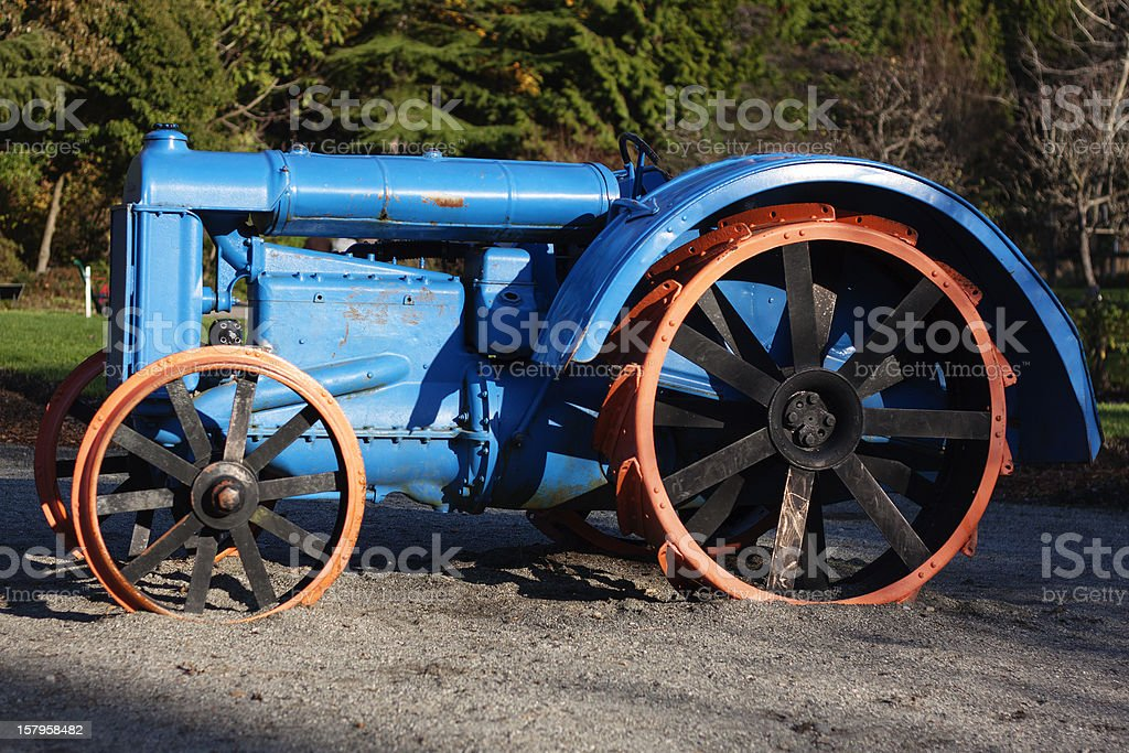A big, blue toy tractor with orange wheels in a public park. stock photo