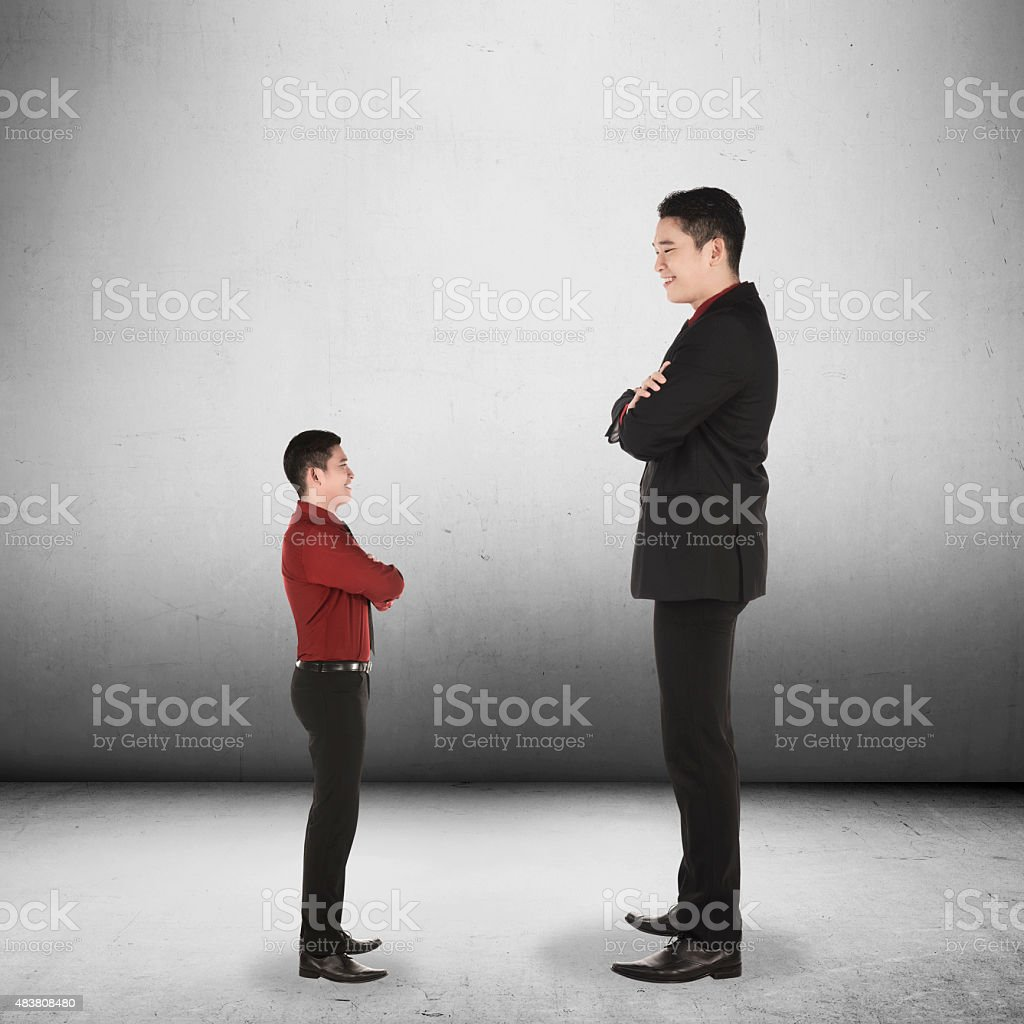 Big boss looking at smaller worker stock photo
