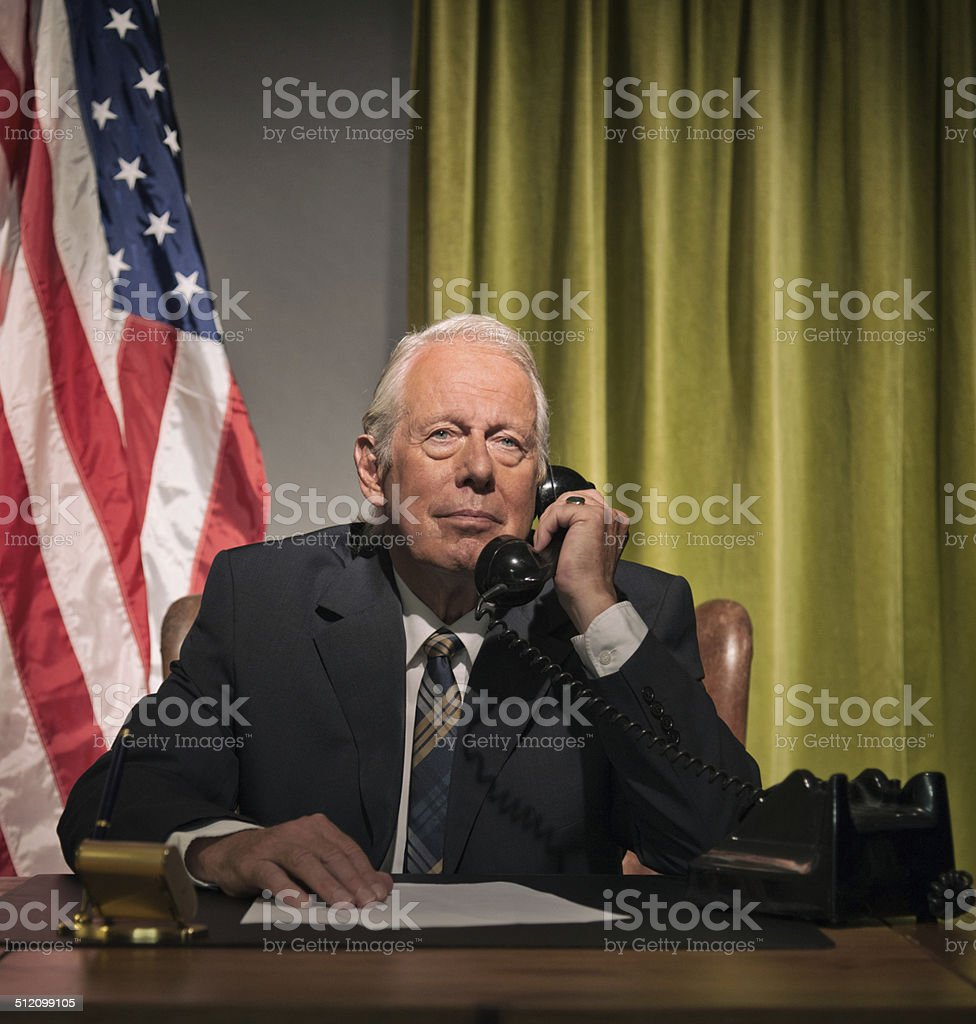 Big boss president calling behind desk with american flag. stock photo