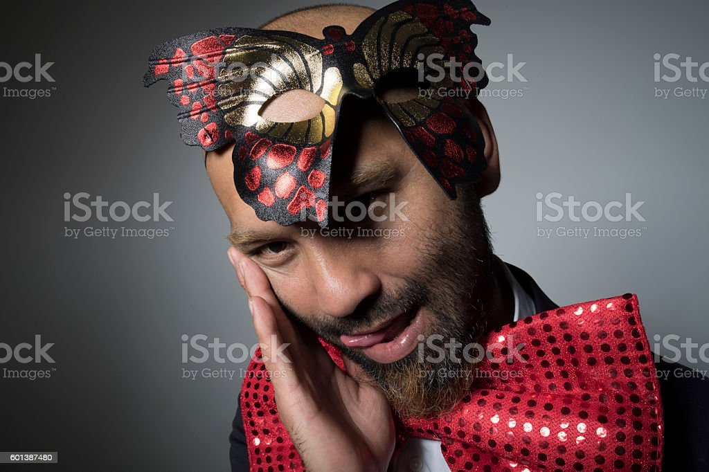 Big bow tie and a mask and a strange man. stock photo