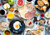 Big breakfast on the white rustic table.