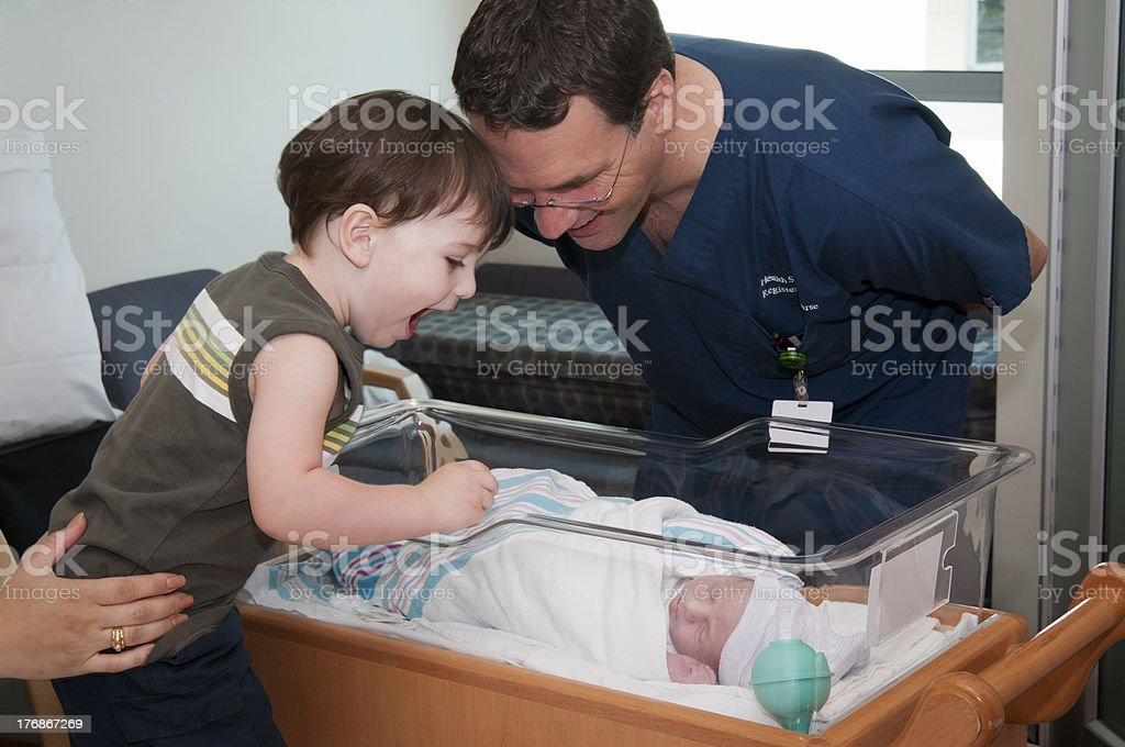 big brother and male nurse admiring newborn baby stock photo