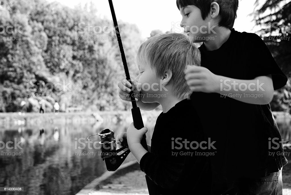 Big Brother helping little Boy Fish stock photo