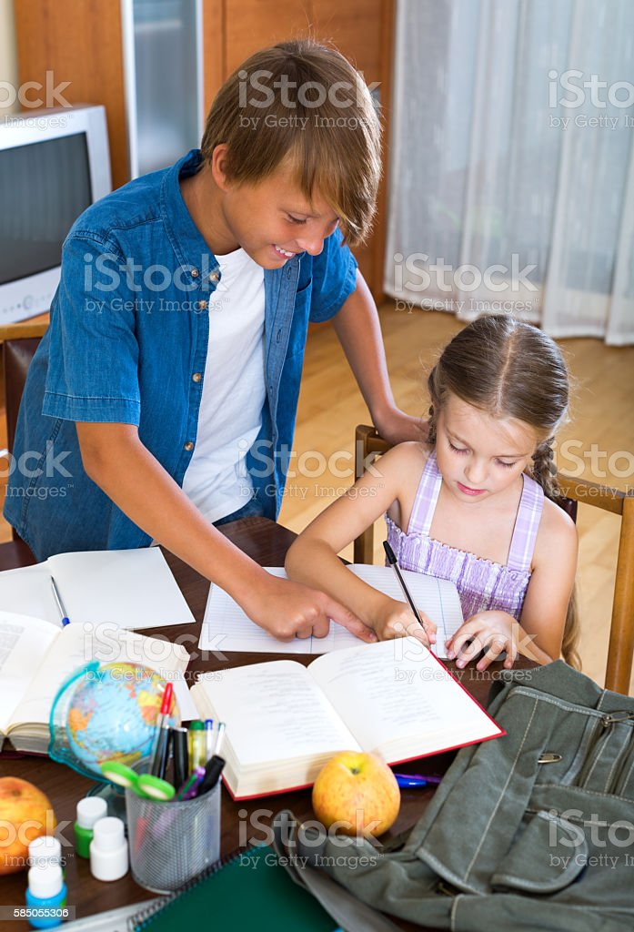 Big brother helping little girl stock photo