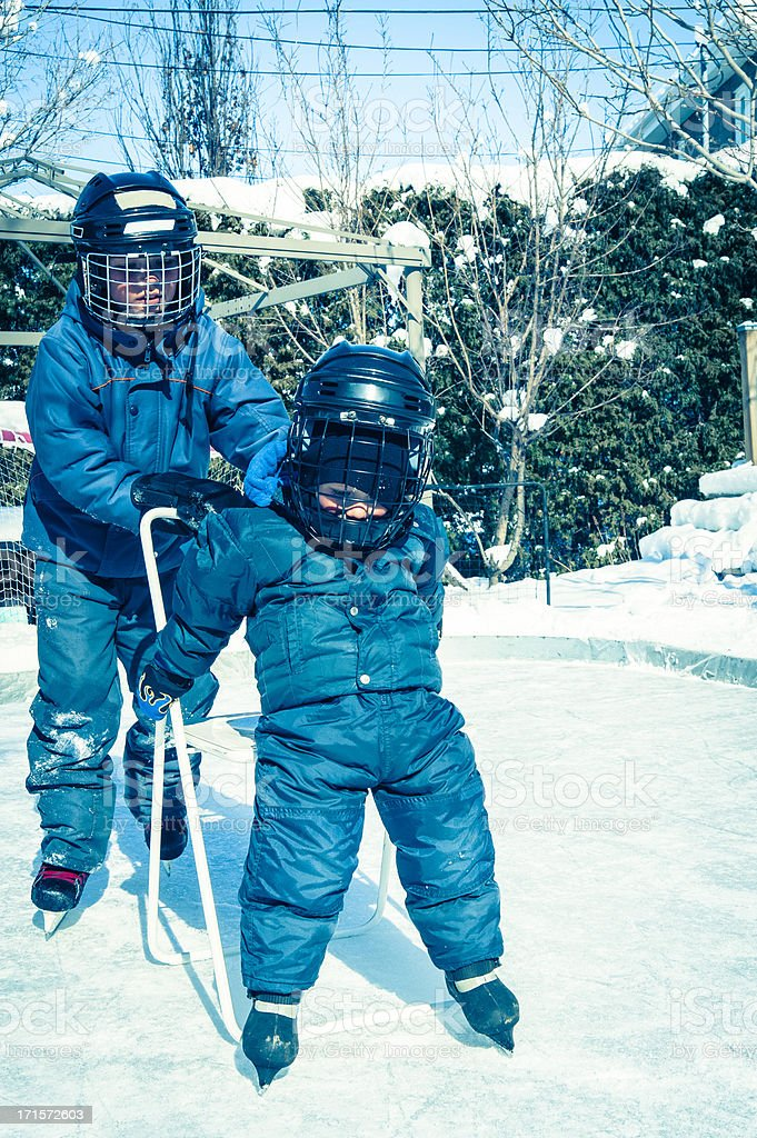 Big brother helping little one on the backyard ice rink. royalty-free stock photo