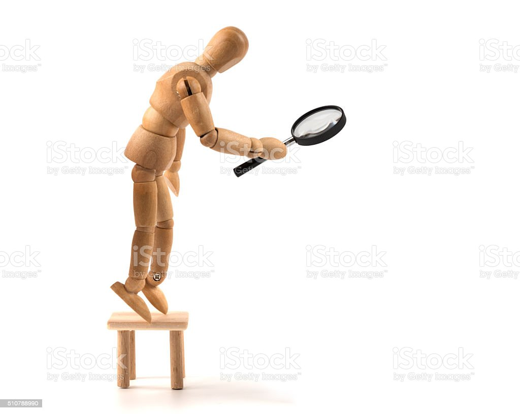 big brother is watching you - wooden mannequin magnifier stock photo