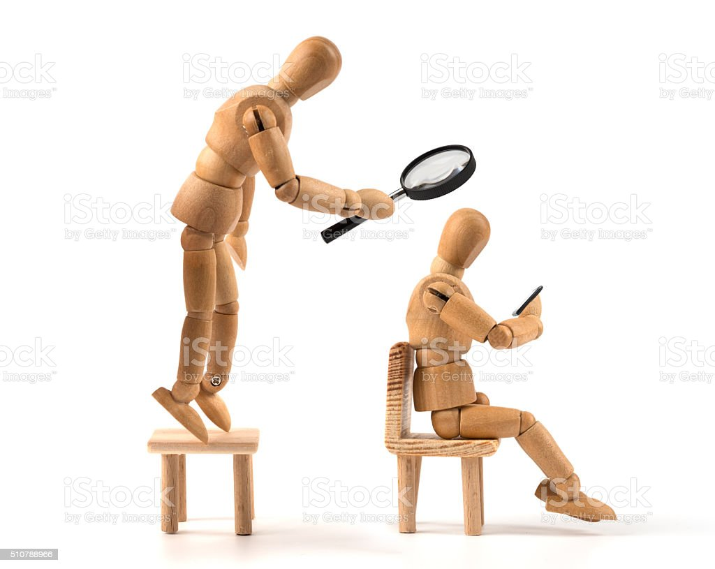 big brother is watching your data - wooden mannequin smartphone stock photo