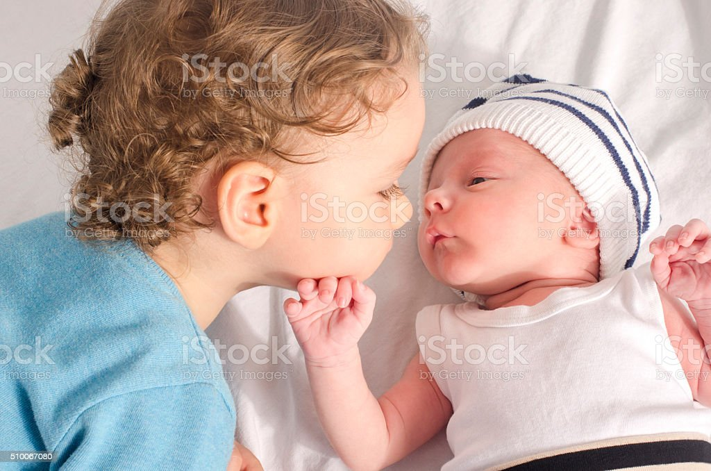 Big brother kissing his little sibling. stock photo