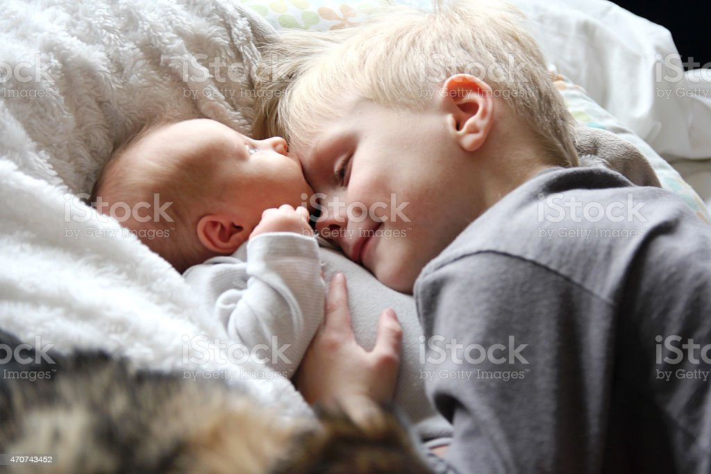 Big Brother Looking at Newborn Baby with Love stock photo