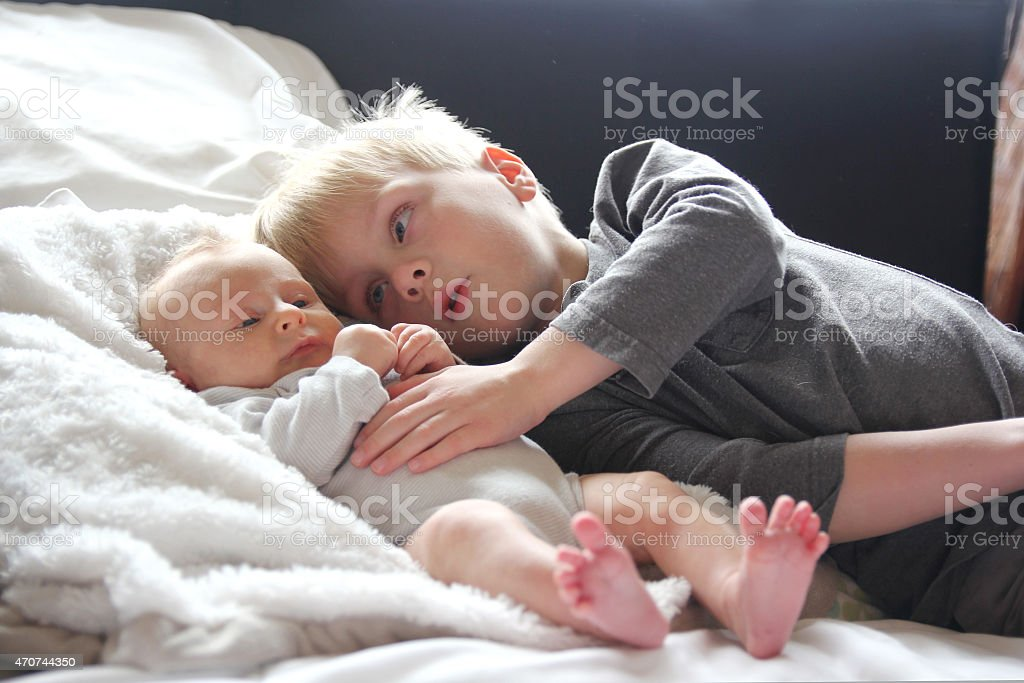 Big Brother Lovingly Playing with Newborn Baby Sister stock photo