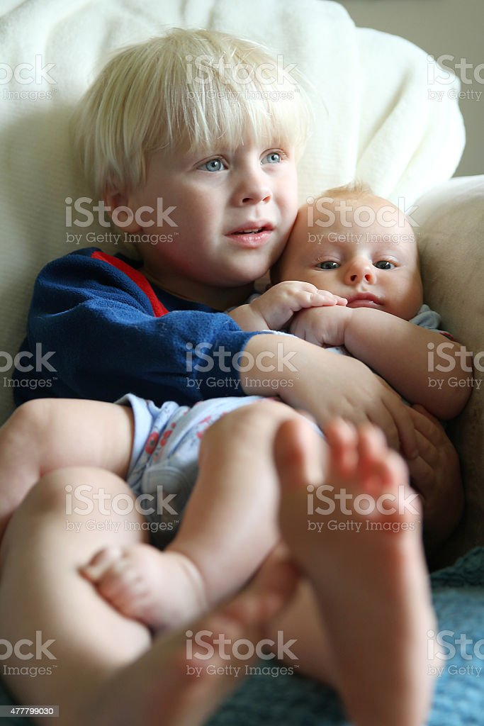Big Brother Snuggling Baby Sister stock photo