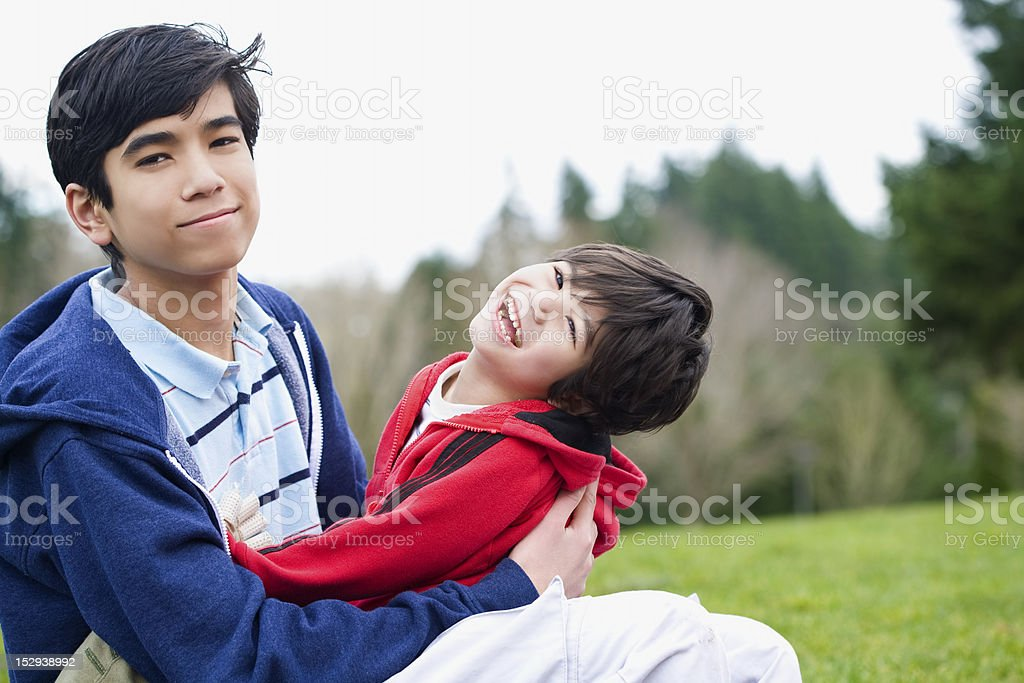 Big brother taking care of disabled little sibling royalty-free stock photo