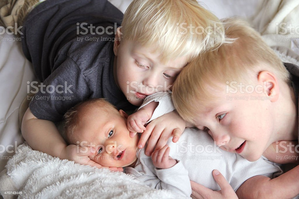 Big Brothers Hugging Newborn Baby Sister stock photo