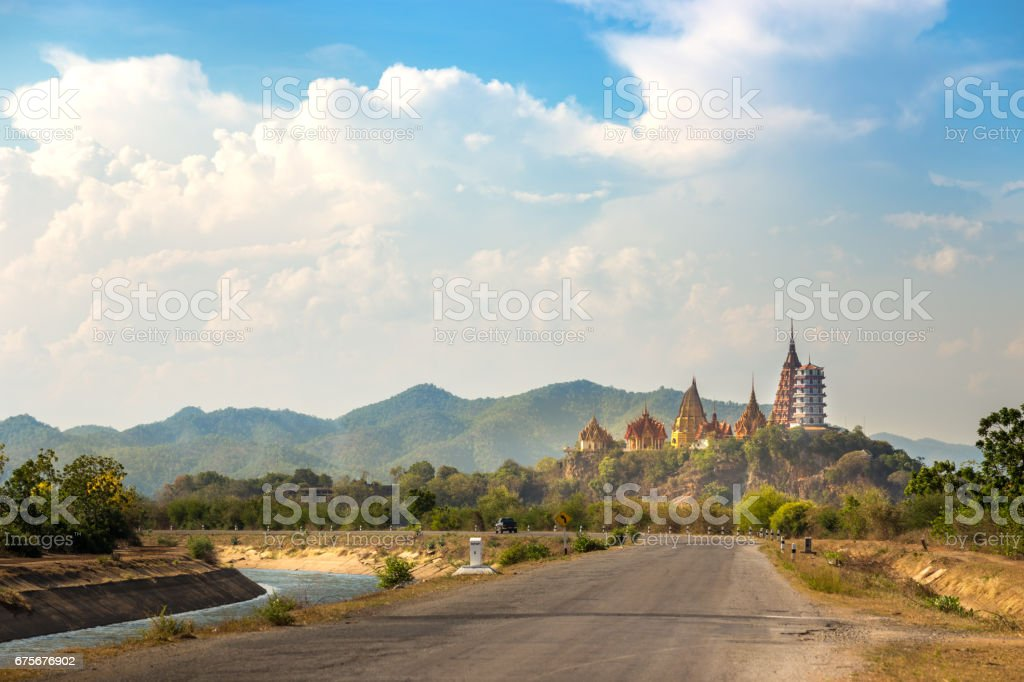 big Buddha temple, Wat Tham Suea, on mountain with view from road and river in Kanchanaburi Thailand stock photo