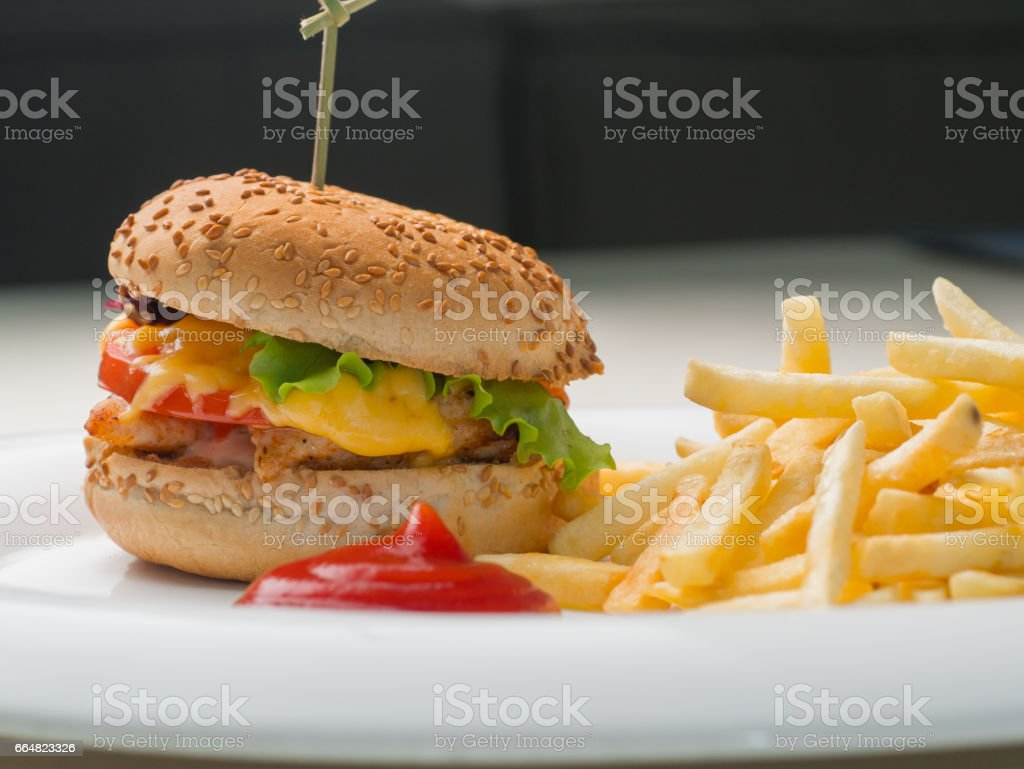 Big burger with french fries and ketchup on white plate stock photo