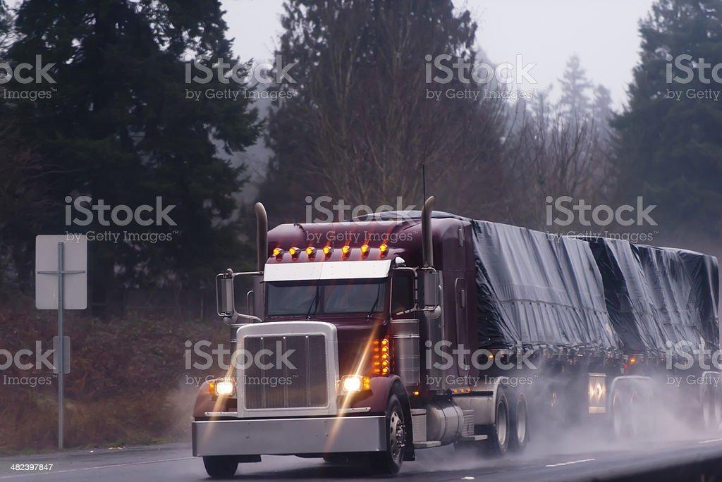 Big burgundy rig in rain on high way stock photo
