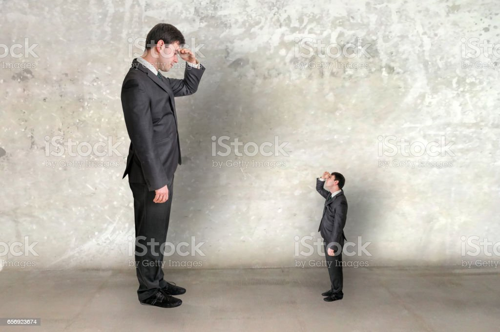 Big businessman and small businessman watch each other stock photo