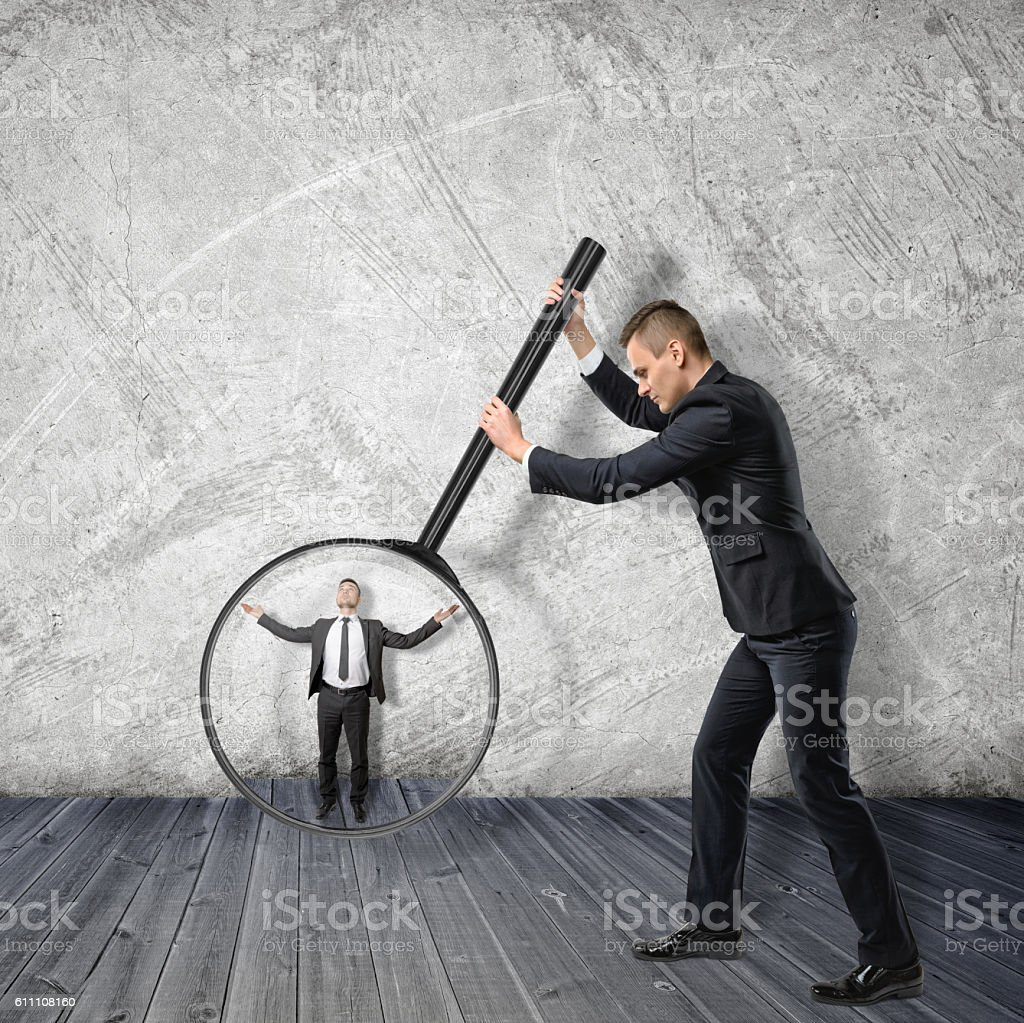 Big businessman enlarging small with magnifying glass stock photo