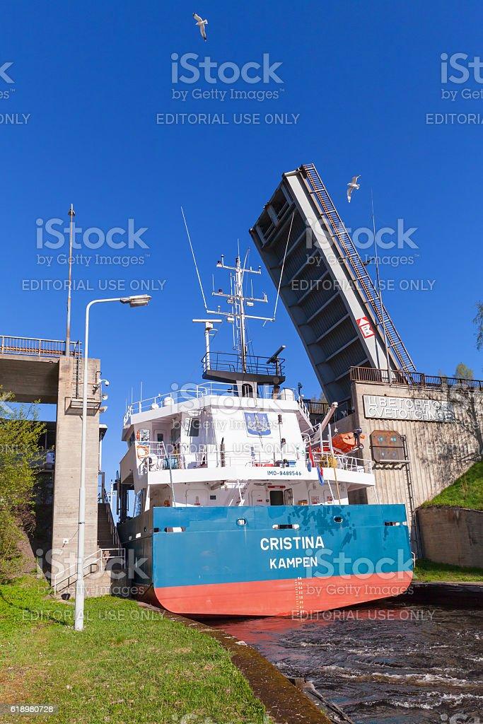 Big cargo ship goes under open bridge stock photo