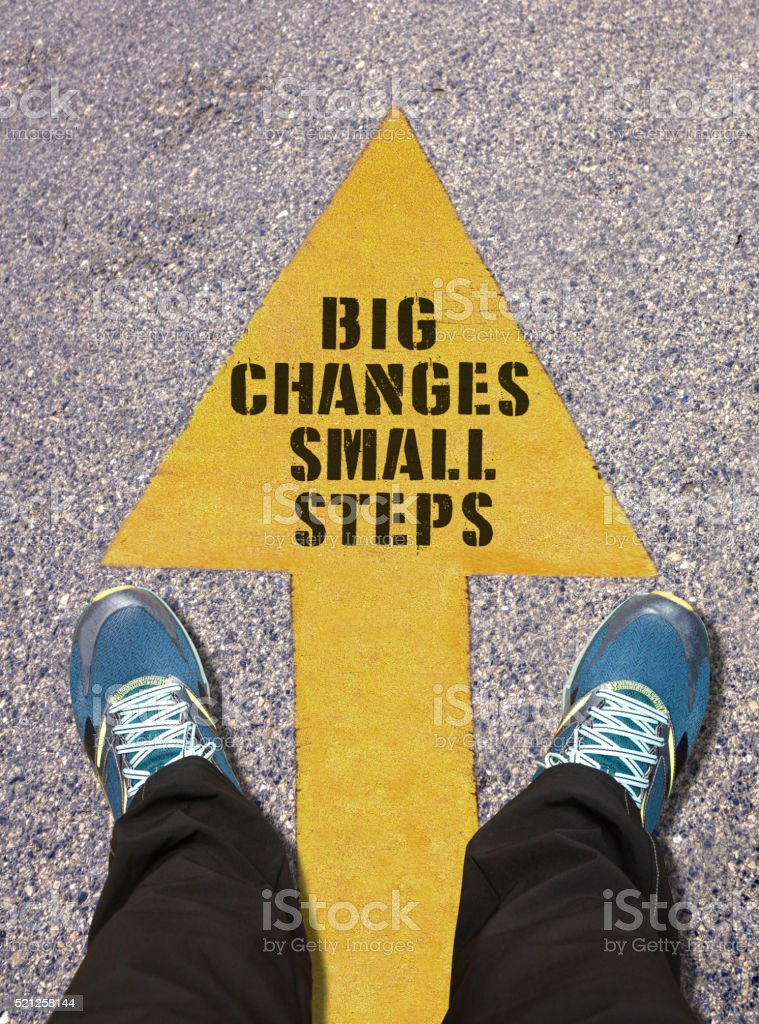 Big Changes Small Steps Message painted on road stock photo