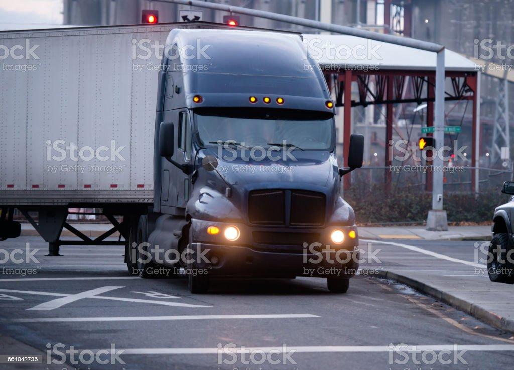 Big classic modern dark rig semi truck with reefer trailer make a turn on the city road with railroad crossing barrier stock photo