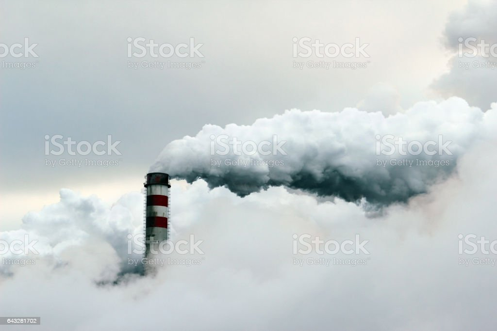 big cloud of smoke coming out of  power plant chimney stock photo