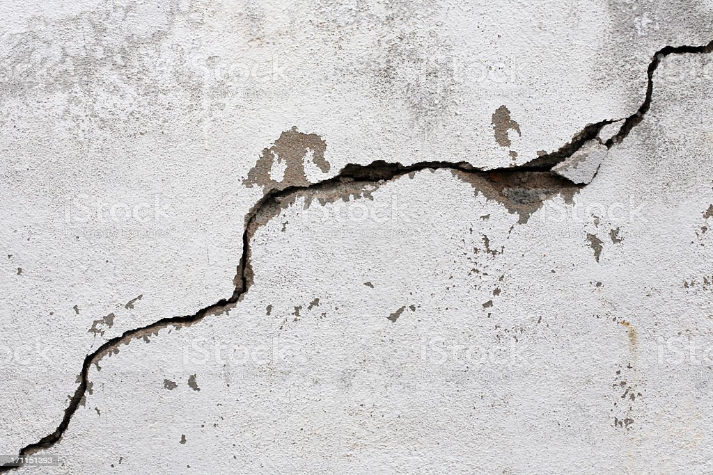 A big crack on an old, rotten wall stock photo
