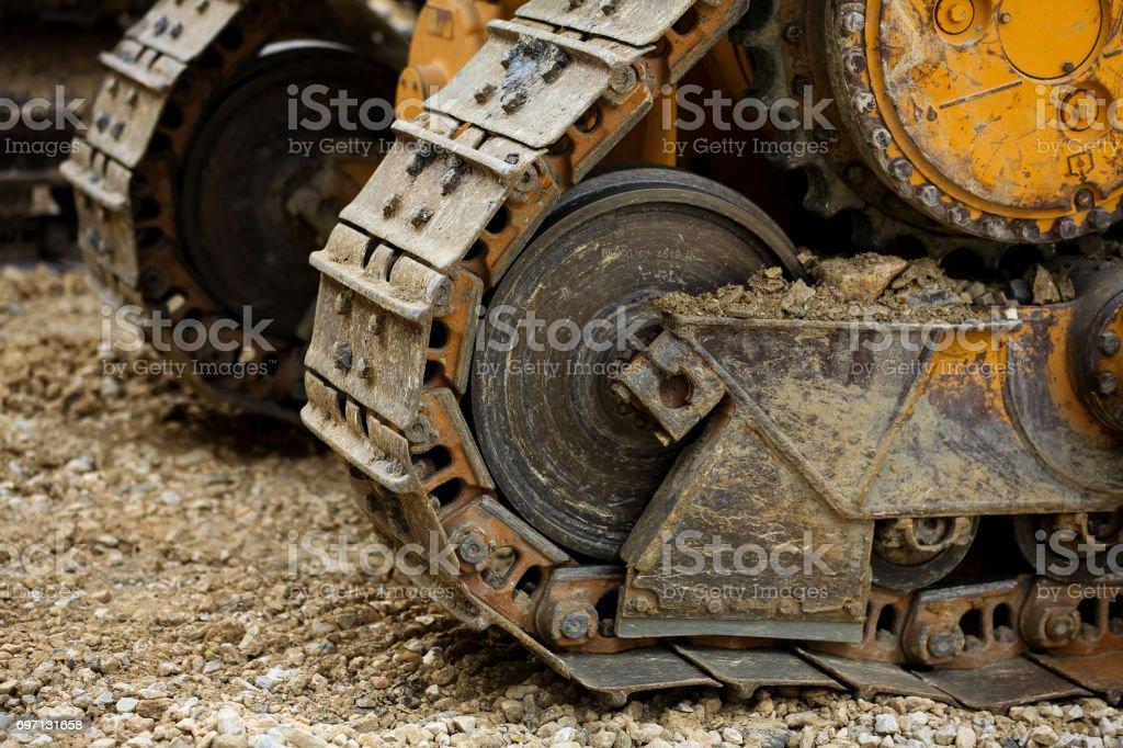 big crawler wheel, The Crawler close up , muddy crawler chain detail in earthy ambiance, Well used excavator tracks closeup stock photo