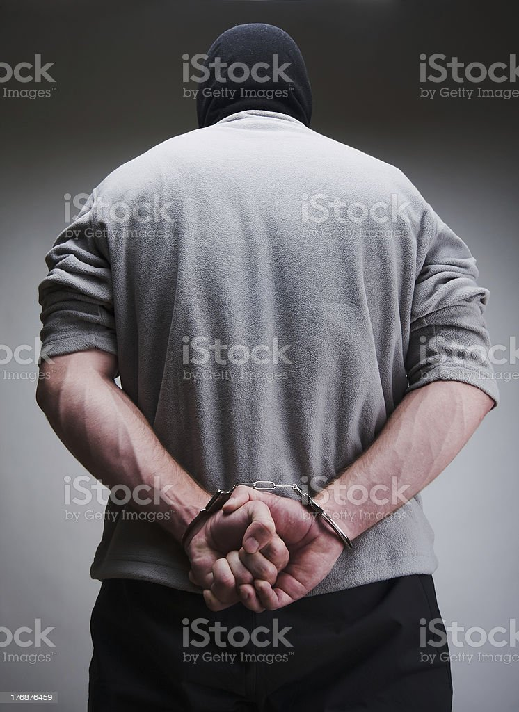 Big criminal locked in handcuffs royalty-free stock photo