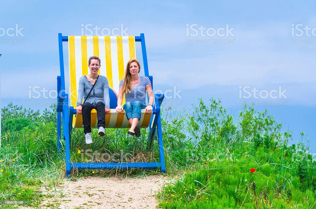 Big deck chair with 2 women stock photo